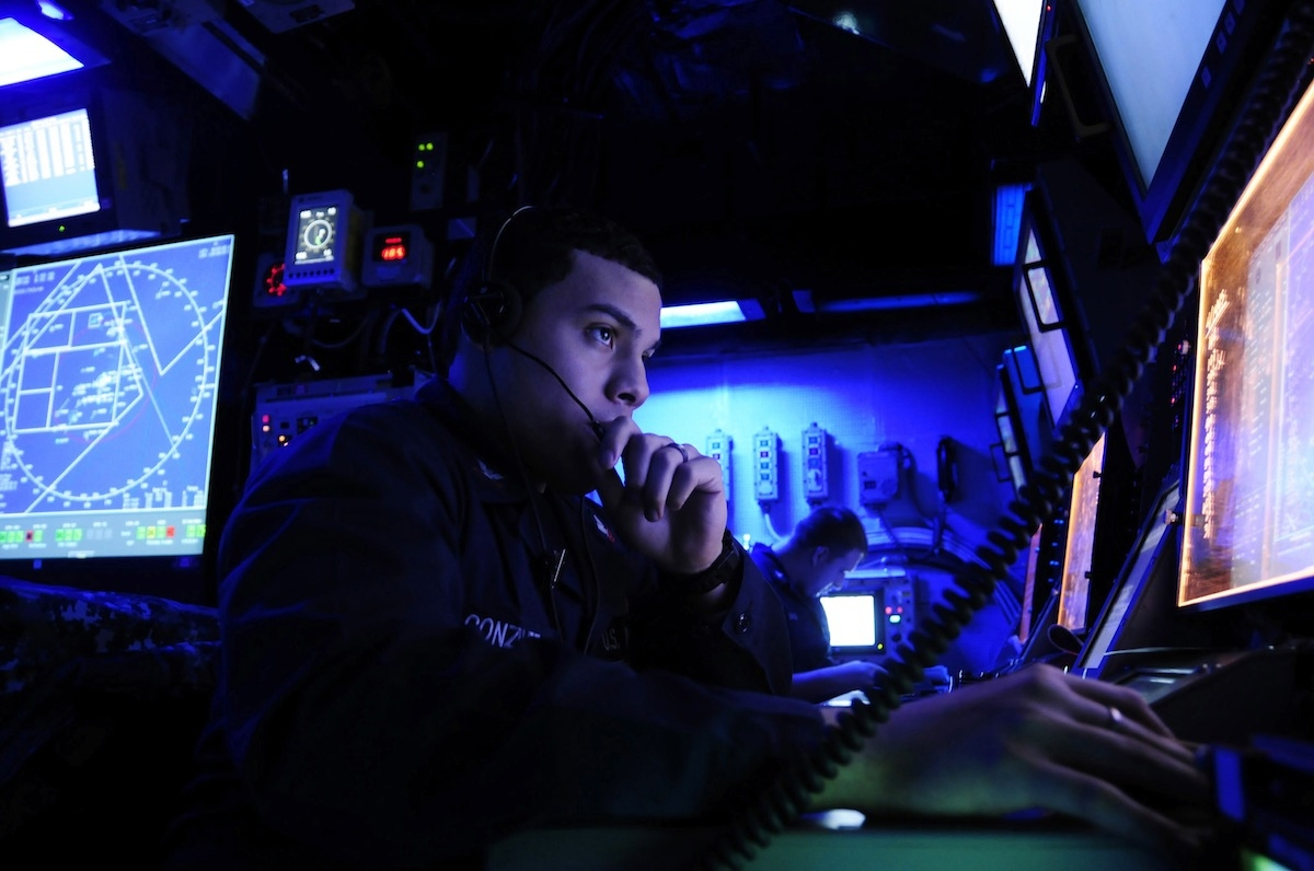 Operations Specialist 2nd Class Marcus Gonzalez stands watch in the Combat Direction Center (CDC) aboard the aircraft carrier USS George Washington